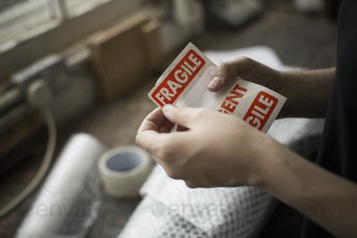 Hands holding a red Fragile sticker to stick it on a brown paper package on a work bench.