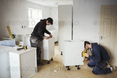 Two builders, building white kitchen units.