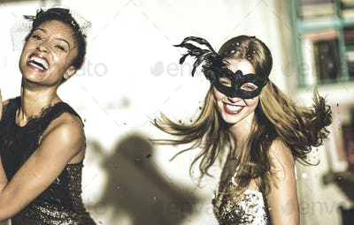 Two young women at a party in sequined dresses drinking and laughing, one wearing a face mask.