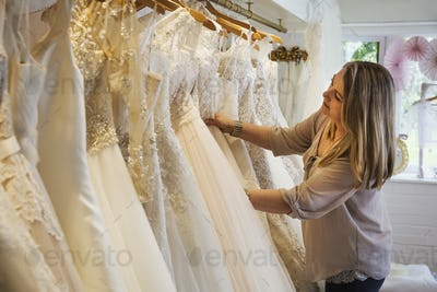 A sales assistant in a wedding dress shop, looking through the gowns hanging in the rails.