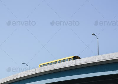 A yellow schoolbus driving over an elevated roadway against a blue sky.