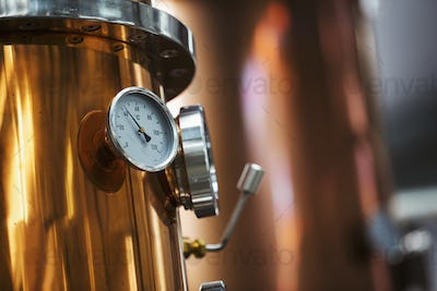 Close up of a gauge on a copper brew kettle or fermentation chamber.