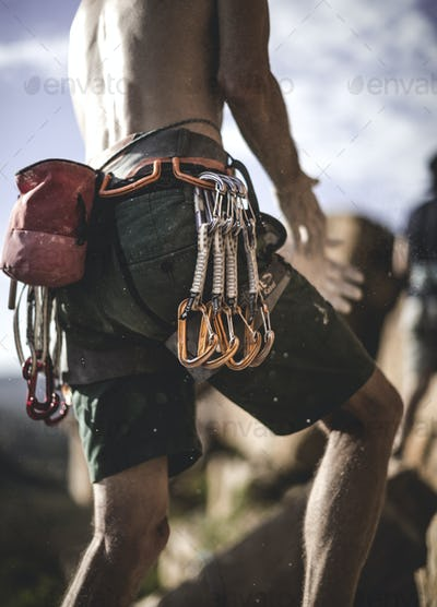 Close up of a mountaineer wearing rope, carabiners, and carabiners on his belt.