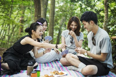 Three young women and a man sitting in a forest, playing cards.