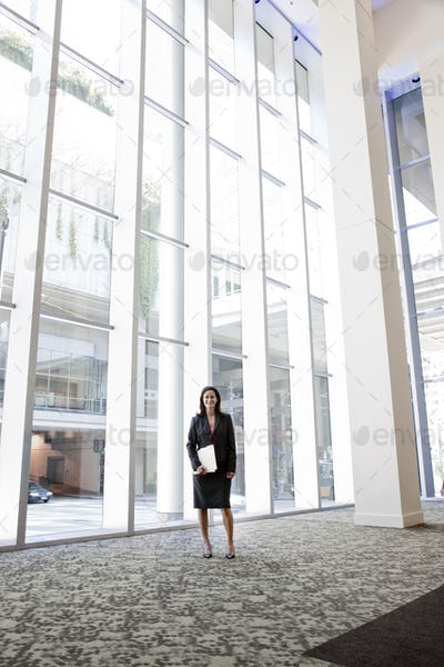 Businesswoman standing in the lobby of a large business center.