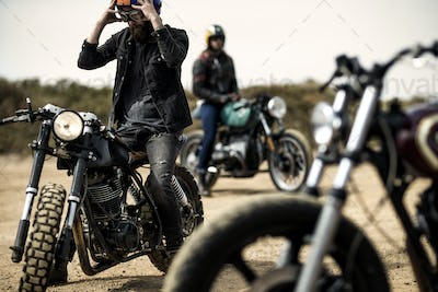 Three men sitting on cafe racer motorcycles on a dusty dirt road.
