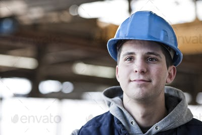 View of a young caucasian factory worker wearing a hard hat in a factory.