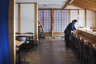 Waitress standing at a counter in a Japanese sushi restaurant, preparing place settings.