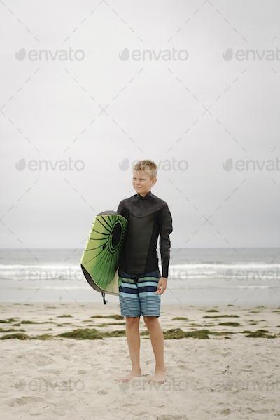 Blond boy standing on a sandy beach, holding a bodyboard.