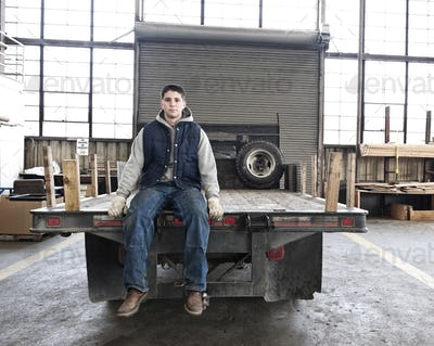 A young caucasian factory worker sitting on the back of a flat bed truck in a sheet metal factory.