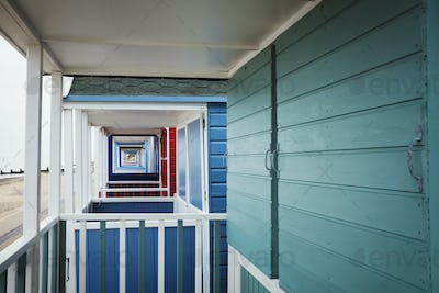The terraces of a row of wooden painted beach huts on a beach in England.