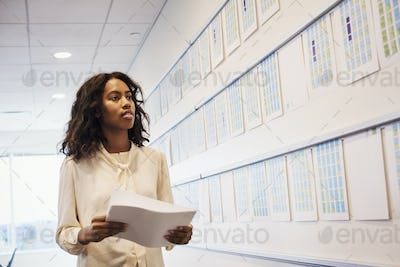 A woman standing in an office looking at a display holding pieces of paper.