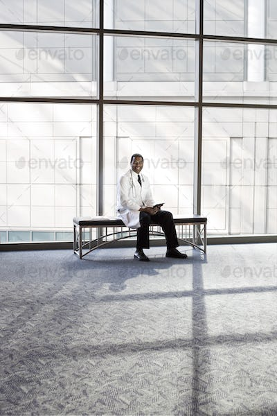Black man doctor in lab coat with stethescope.