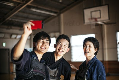 Smiling female and two male Japanese Kendo fighters standing in a gym, taking selfie with mobile