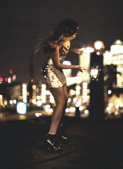 A young woman holding a sparkler and dancing on a building rooftop at night