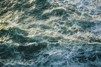 Crashing waves and surf, green and turquoise colours in the ocean, view from above.