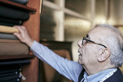 A man with grey hair and glasses reaching up to select fabrics from the choice of cloth.