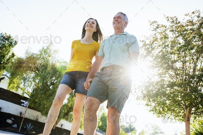 Senior couple wearing shorts walking along a street in the sunshine.