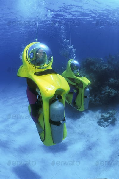 Two divers in Breathing Observation Submersible Scooters, underwater vehicles moving through the