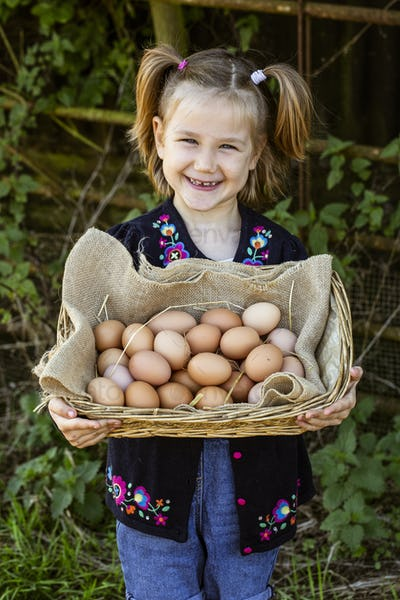 Smiling girl holding basket with eggs, looking at camera.