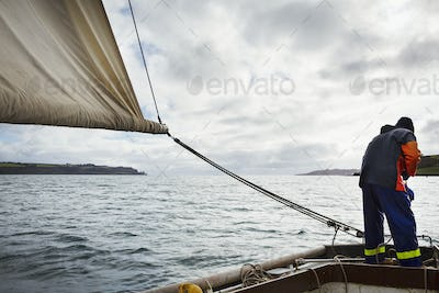 Traditional Sustainable Oyster Fishing, a fisherman on a sailing boat in the Fal Estuary.