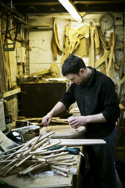 A man working in a furniture maker's workshop. Chairlegs on the bench.