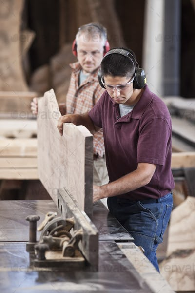Team of two caucasian men cutting a large  wooden slab on a table saw in a woodworking factory.