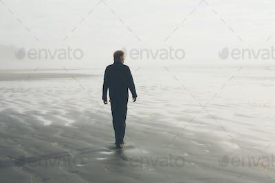 Middle aged man walking on a beach at Seabrook, Washington, USA.