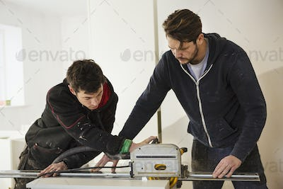Two builders, cutting plasterboard with a circular saw.