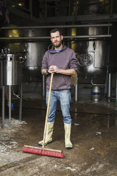Man working in a brewery, cleaning floor with a large broom.