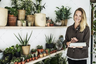 Female owner of plant shop standing next to a selection of plants on wooden shelves, holding digital