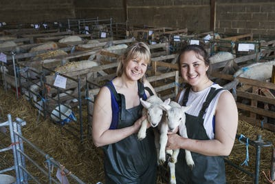 Two smiling women standing in a stable, holding newborn lambs.