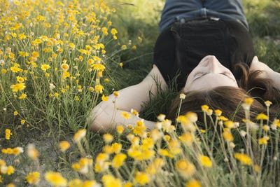 A woman in a black vest top and jeans lying on the grass with her hands behind her head.