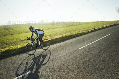 A cyclist riding along a country road on a clear sunny winter day. Shadow on the road surface.
