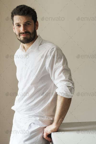 Half length portrait of a bearded man wearing a white apron, smiling at the camera.