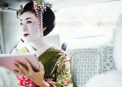 A woman dressed in the traditional geisha style, wearing a kimono with an elaborate hairstyle and