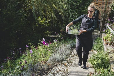 Smiling blond woman wearing glasses and apron walking along garden path, carrying tray with fresh