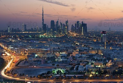 Cityscape of the Dubai, United Arab Emirates at dusk, with highway in the foreground and skyscrapers