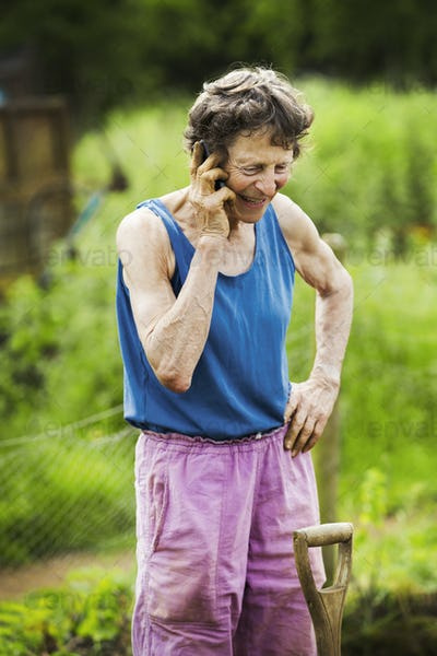 A woman talking on the phone with a shovel by her leg in a farm.