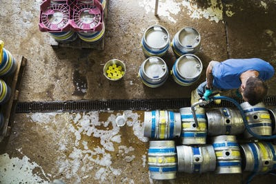 Directly above view of a man working in a brewery, metal beer kegs standing on the floor.