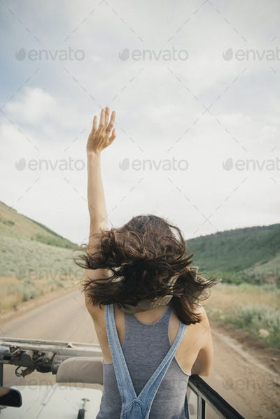A woman with her arm raised standing in a jeep on a mountain road