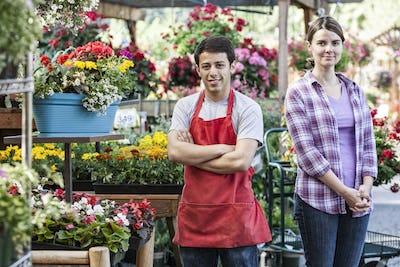 Caucasian man and woman employees of a garden center nursery.