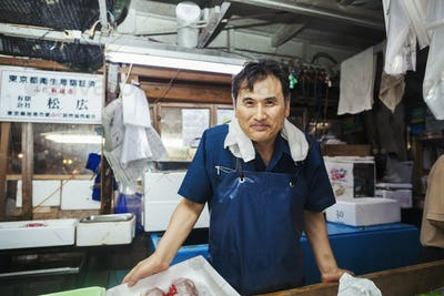 A traditional fresh fish market in Tokyo. A man in a blue apron standing behind the counter of his