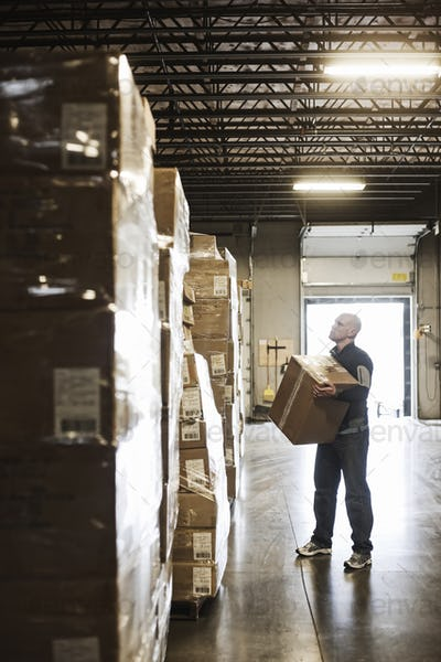 Caucasian male  waehouse worker checking inventory on stacks of cardboard boxes holding products in