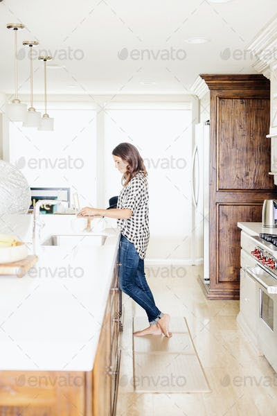 Woman with long brown hair, wearing a chequered shirt, standing in a kitchen.