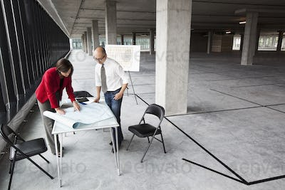 Asian architect with caucasian woman planning workspaces in a new raw office location