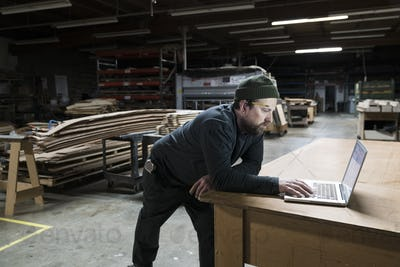 A Caucasian carpenter working on his lap top after hours in a large woodworking factory.