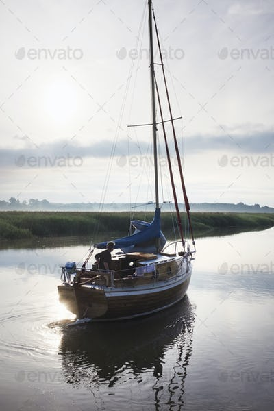 Man on sailboat on river.