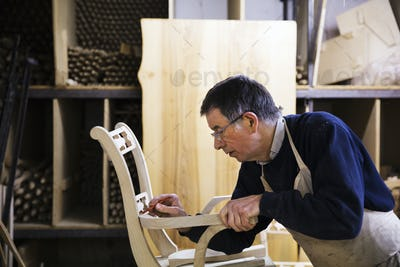 Man standing in a carpentry workshop, working on a wooden chair marking the armrest joint with a