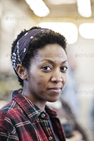 Black woman wearing a bandana in a factrory.